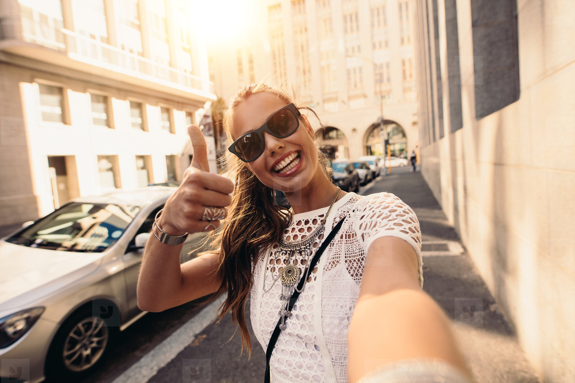 Tourist taking selfie in a street surrounded by buildings