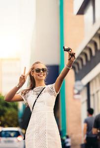 Tourist taking selfie in a street using a digital camera