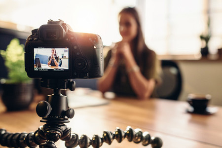 Digital camera on flexible tripod recording a video of woman at