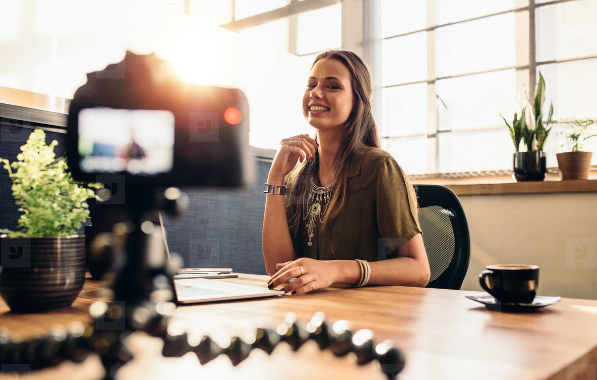 Young female vlogger recording content for her video blog