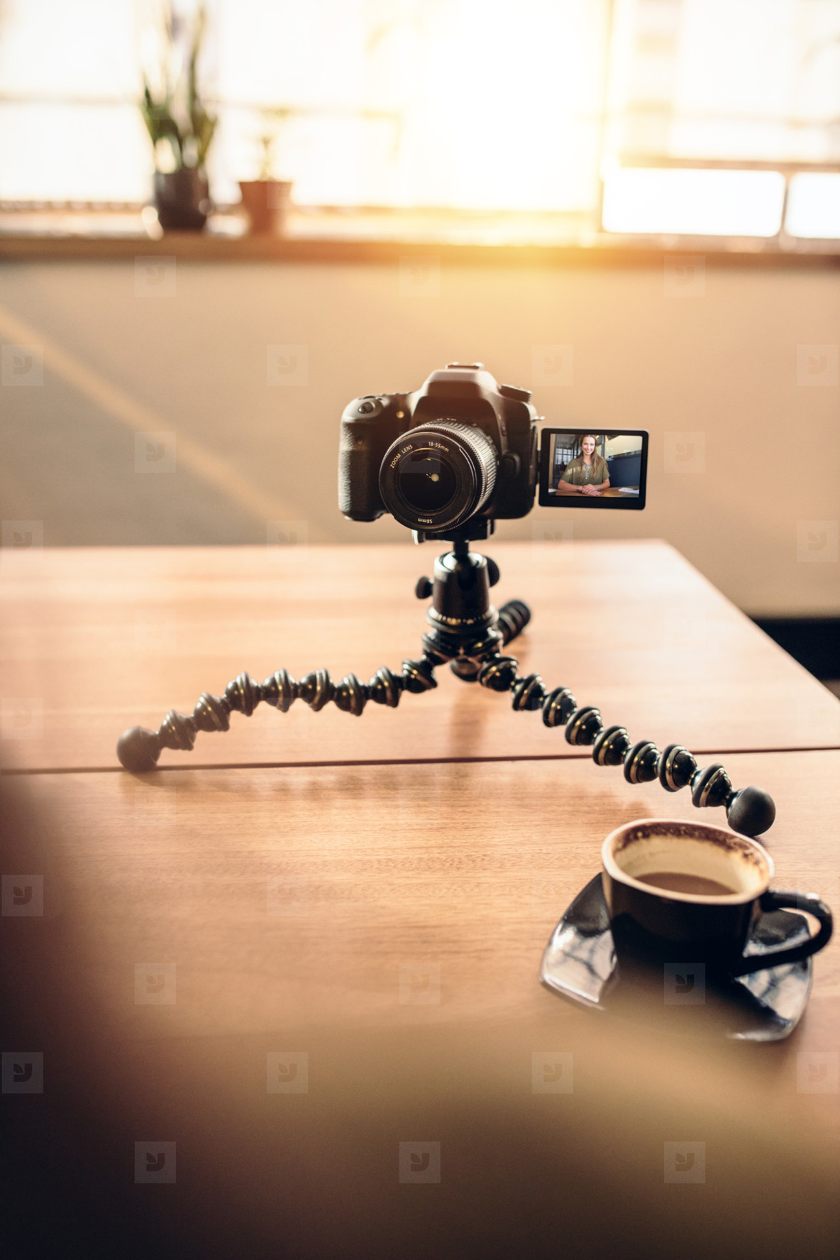 Desk of a photographer with coffee and tripod mounted digital ca