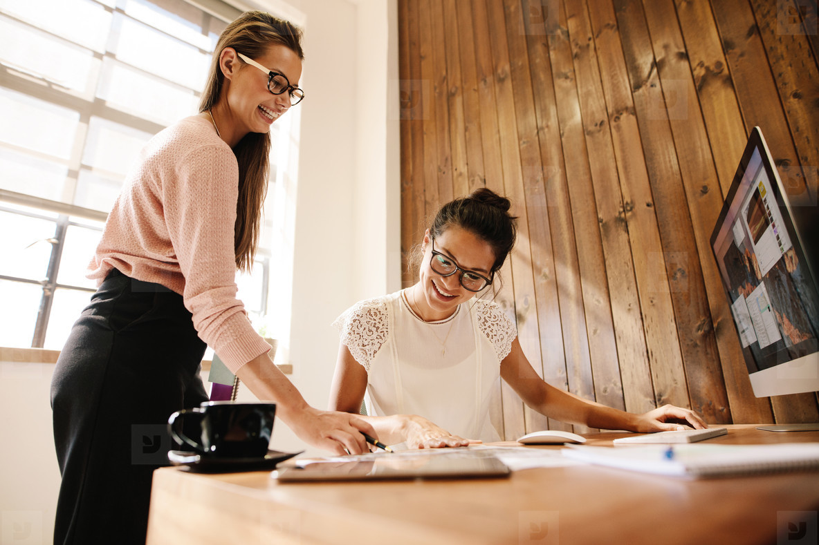 Smiling creative business women at the office desk