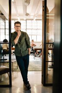 Handsome young man standing in office doorway