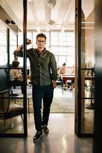 Young man standing in doorway at startup office