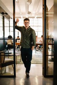 Happy young businessman standing in office doorway