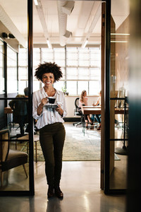 Smiling woman standing in office doorway with coffee