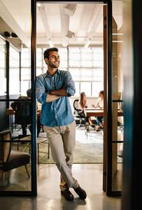 Happy young man standing in office doorway