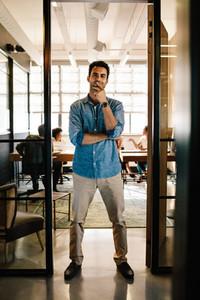 Creative young man standing in doorway
