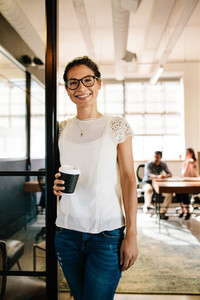 Relaxed woman in office doorway with coffee