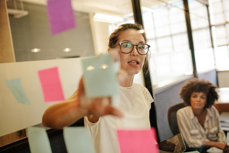 Businesswoman pointing at sticky note to colleague