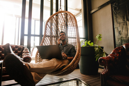 Business man relaxing in office lounge during break
