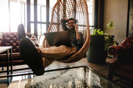 Male executive in office lounge taking break