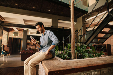 Happy young man in modern office lounge using mobile phone