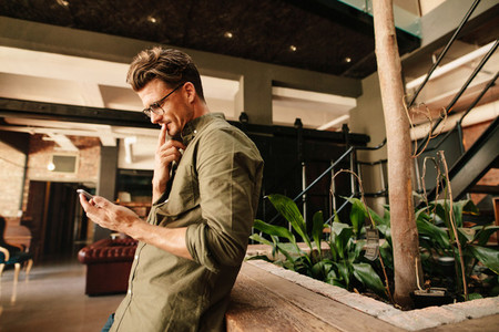 Thoughtful businessman using mobile phone in office lobby