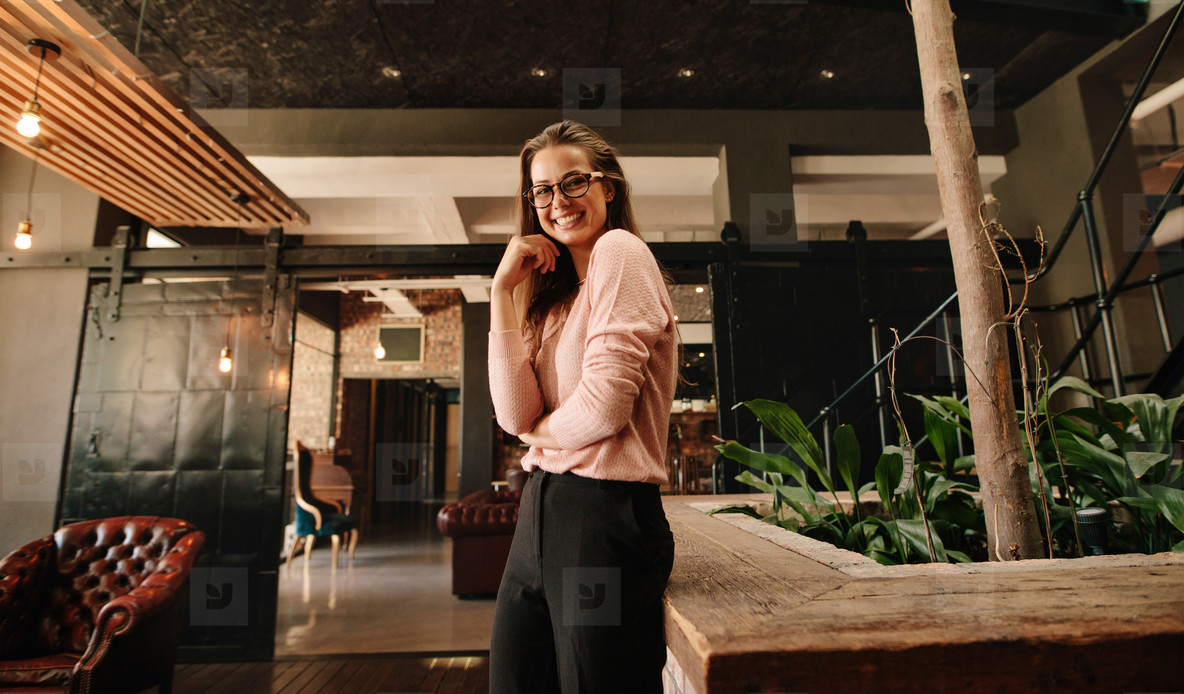 Business woman in office lobby looking happy