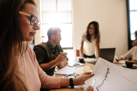 Woman looking at document during meeting in conference room