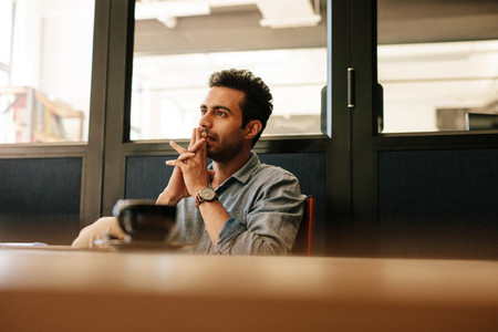 Thoughtful young man sitting at table in conference room