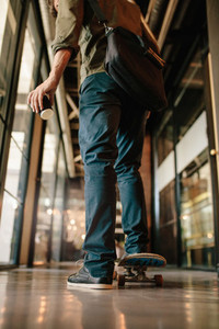 Man with skateboard in office