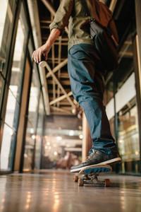 Man skateboarding in office corridor