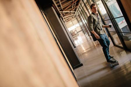Handsome young man skateboarding in office corridor