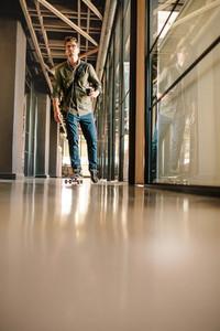 Casual businessman skating through office corridor