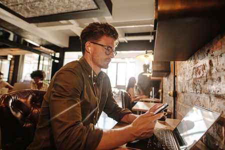 Casual businessman at cafe using cell phone