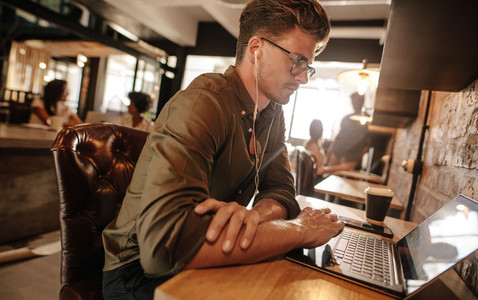 Young man sitting at startup using laptop