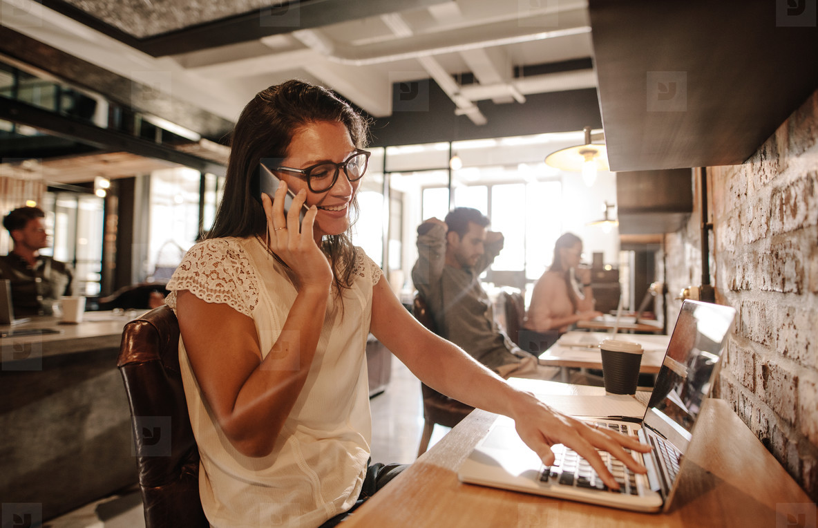 Happy Businesswoman At Office Talking On Mobile Phone