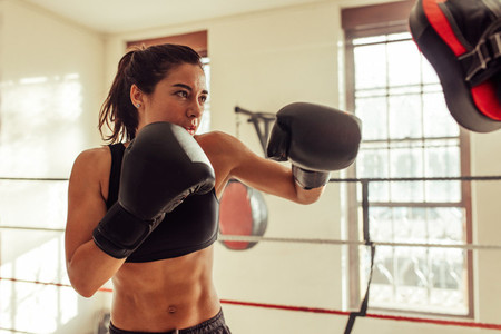 Serious fit woman punching focus pads