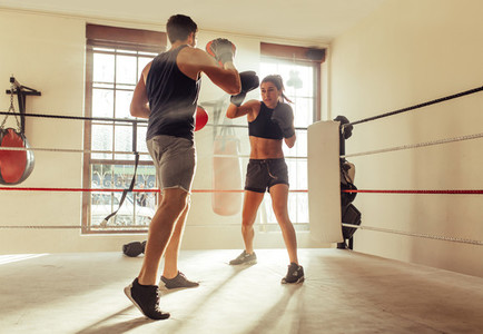 Trainer helping boxer with striking techniques