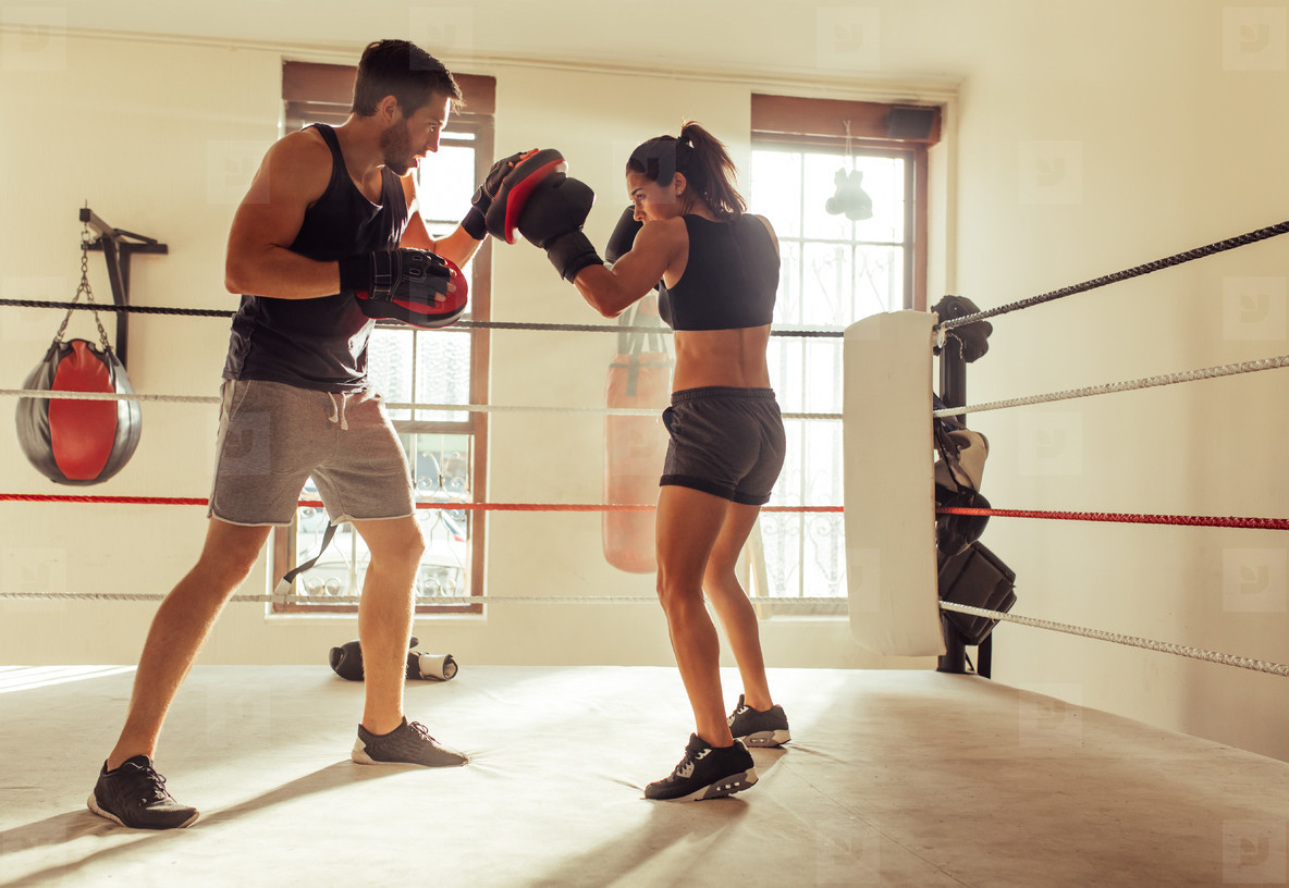 Boxer with trainer practicing punching techniques