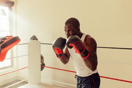 Focused young male boxer practicing