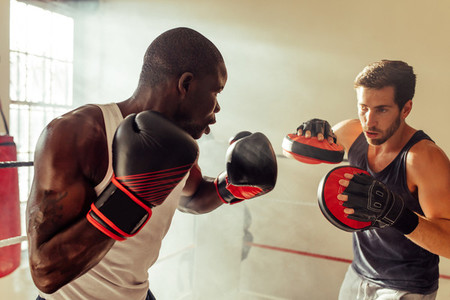 Boxing trainer with athlete practicing in gym