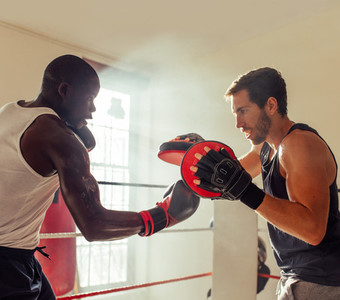 Boxer practicing uppercut punches with trainer