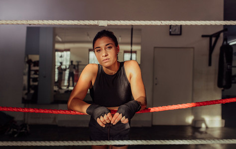 Serious female boxer leaning on ropes