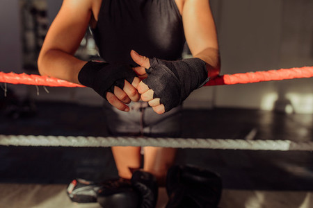 Hands wrapped in black near boxing ring rope