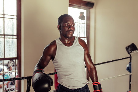 Sweating Black man leaning on boxing ring rope