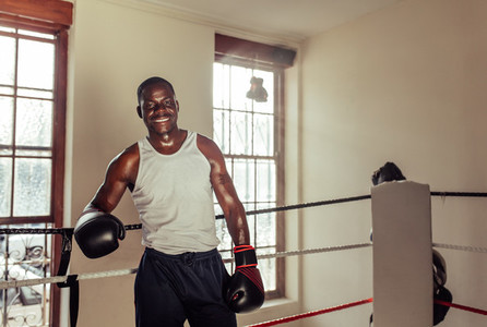 Happy sweaty fit young African boxer