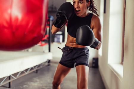 Action shot of woman training on red punching bag