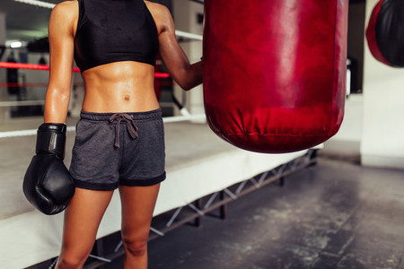 Young female boxer posing with a punching bag