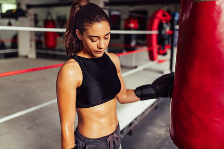 Tired sweaty attractive young female boxer