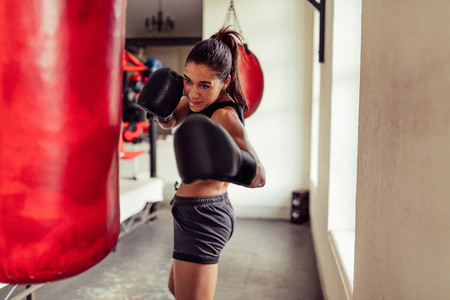 Fit young woman boxer punching a bag in the gym