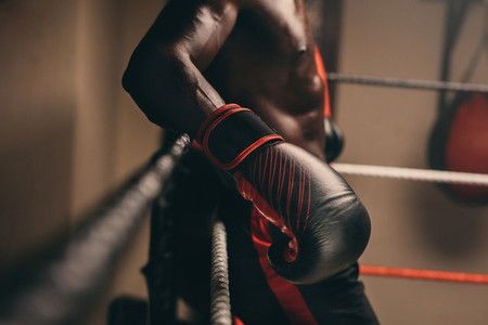 Boxer relaxing against the ropes between rounds