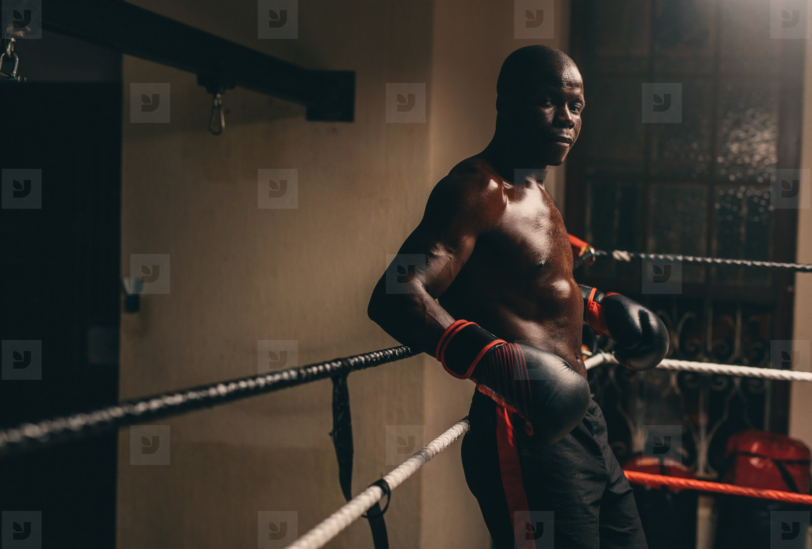 Muscular young African boxer resting in his corner