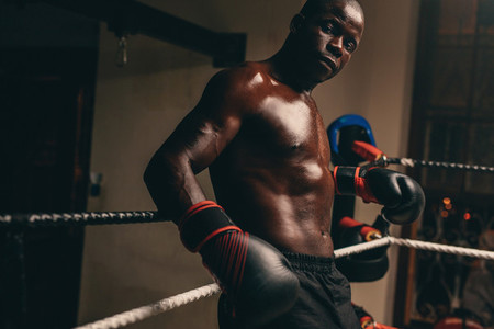Male boxing relaxing in the corner of the ring