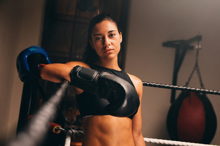 Female athlete stands against ropes in boxing ring