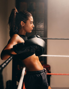 Young muscular female boxer leans against ropes