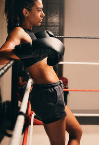Relaxed confident woman boxer leaning on the ropes