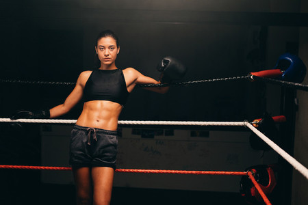 Woman in black shorts and gloves in boxing ring