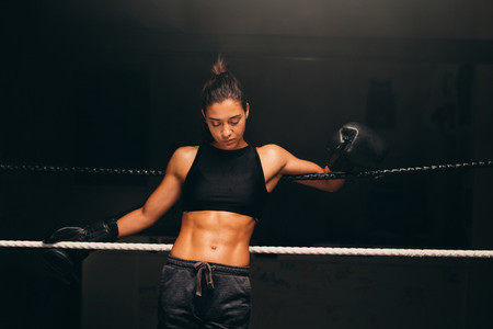 Woman wearing boxing gloves looks down
